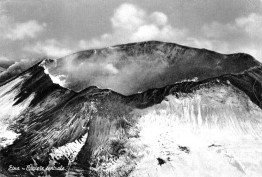 """Figura 1. Vista aerea, intorno al 1920, del Cratere Centrale nella sua forma """"classica"""". Al margine sinistro dell'immagine si vede il pennacchio di gas emesso dal Cratere di Nord-Est, nato nella primavera del 1911. Da una vecchia cartolina postale."""