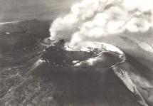 Figura 6. Vista aerea del Cratere Centrale e del Cratere di Nord-Est (sullo sfondo a sinistra) nel 1961, guardando verso nord-est. Nella parte meridionale del Cratere Centrale (in primo piano) si distingue un largo cono piroclastico, formatosi durante le eruzioni parossistiche del 1956 (e forse anche del 1961). Più indietro, la Voragine, che emette un pennacchio di gas (un po' ritoccato), e che è circondata da un campo lavico formato durante l'attività parossistica del maggio 1961. Durante questa attività è avvenuto un trabocco lavico verso nord-nord-ovest (a sinistra). In basso a destra, si può osservare la parte più meridionale della frattura eruttiva del 1949 sul fianco del cono centrale. Dalla collezione privata di Santo Scalia.