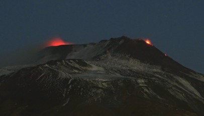 Figura 4. Attività al cratere Bocca Nuova (a sinistra) e alla bocca orientale (Bocca-E) del Nuovo Cratere di Sud-Est (a destra), nelle prime ore del 5 dicembre 2018, vista da Tremestieri Etneo sul versante meridionale dell'Etna. Foto di Boris Behncke.